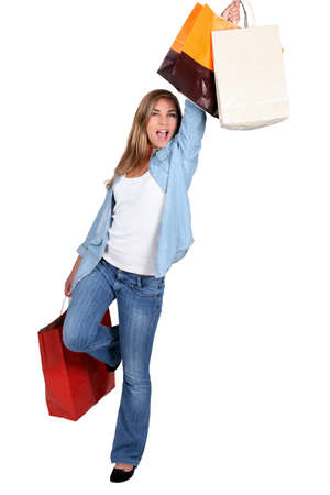 gleeful: Excited young woman with store bags Stock Photo
