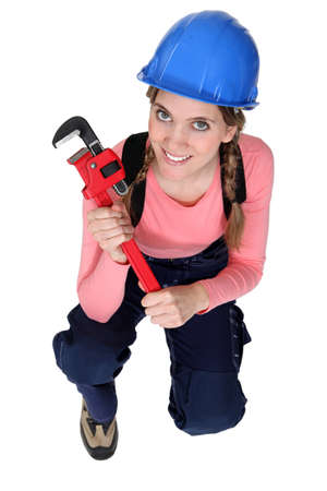 Female plumber kneeling with wrench photo