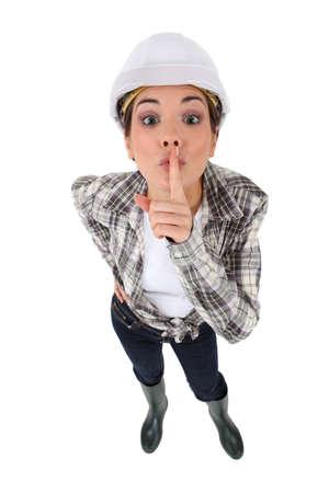 guardar silencio: artesana joven con el dedo antes de la boca para guardar un secreto