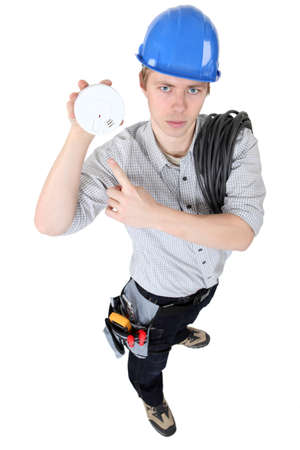 An electrician holding a fire alarm. photo