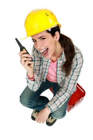 Female construction worker yelling into a walkie-talkie photo