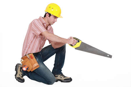 kneel down: young carpenter in profile stretching saw Stock Photo