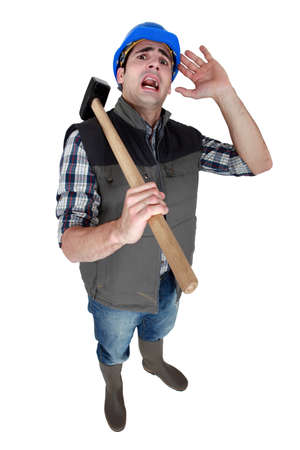 cowering: Scared builder cowering away from camera Stock Photo
