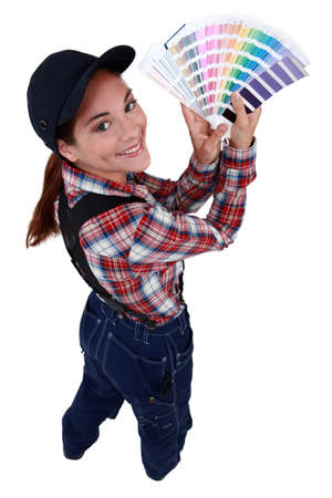 Woman holding up paint colour samples photo