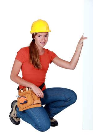 tradeswoman: Tradeswoman holding up a sign Stock Photo
