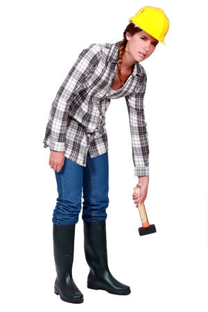 A tired female construction worker with a hammer. photo