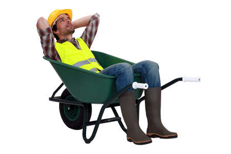 Construction worker resting in a wheelbarrow photo