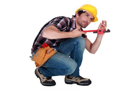 arrodillarse: El hombre con una llave de tubo para apretar un tubo