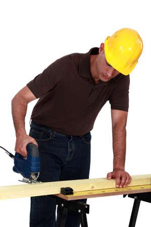 Tradesman using a jigsaw photo