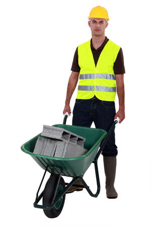 barrow: Man pushing waste material in wheelbarrow Stock Photo