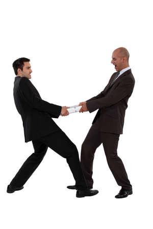 tug o war: Dos hombre de negocios tirando en direcciones diferentes Foto de archivo