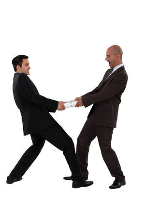 tug of war: Two businessman pulling in different directions