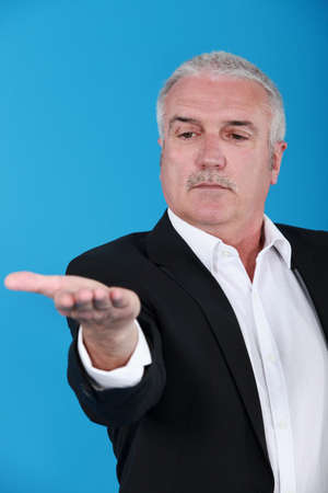 straight faced: Serious man holding out his palm Stock Photo