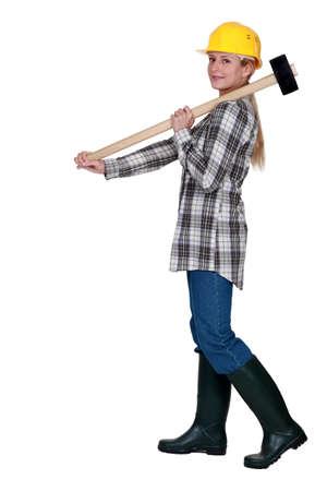 servicewoman: craftswoman holding a huge hammer