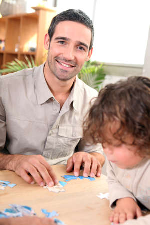Father and child with jig-saw puzzle photo