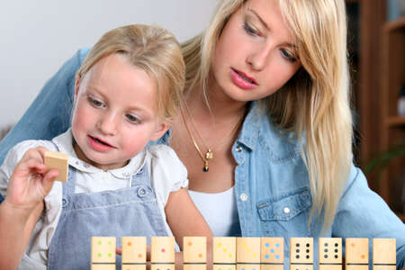 dominoes: Young girl playing with dominoes