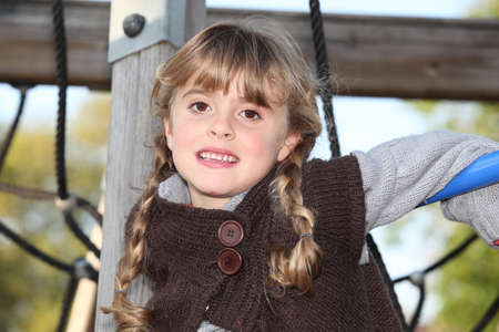 tired little blonde girl in a playground photo