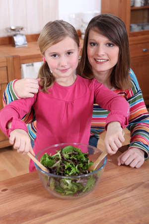 Mother and daughter making a salad together photo