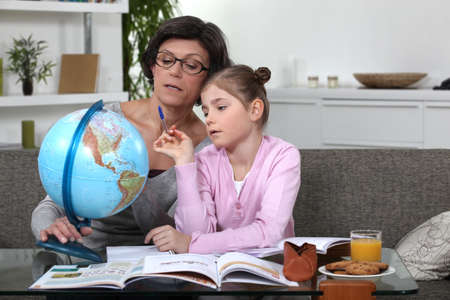 Woman helping her granddaughter complete her geography homework photo