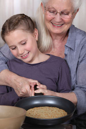 Girl and her granny cooking pancakes photo
