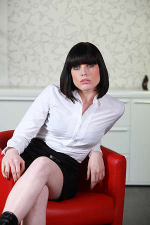 Sultry woman sitting in a red chair photo