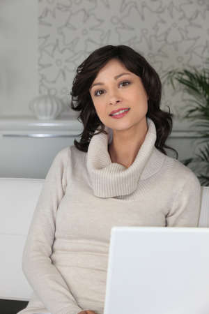 brunette woman behind a laptop in a lounge photo