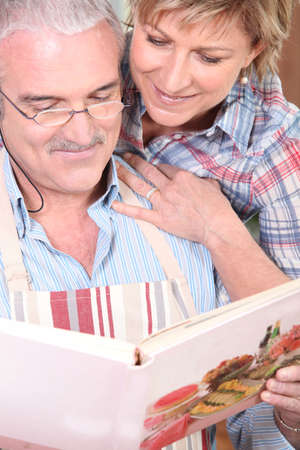 Smiling man and woman selecting recipe on a cookbook photo
