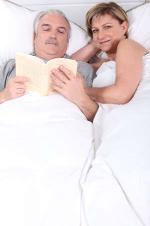 Husband reading next to his wife in bed photo