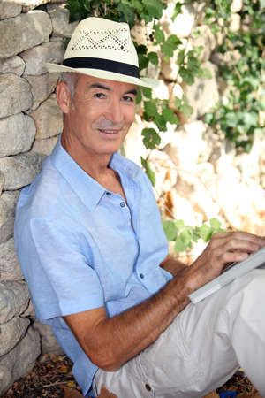 65 years old: Elderly man relaxing in his garden
