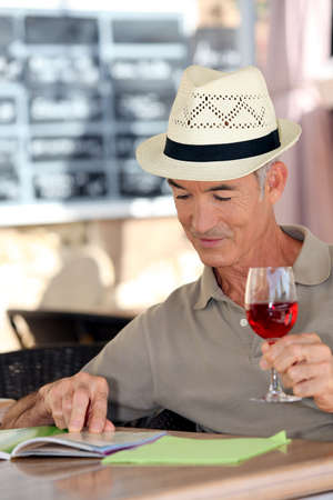 65 years old: Elderly man drinking a glass of rose in a cafe