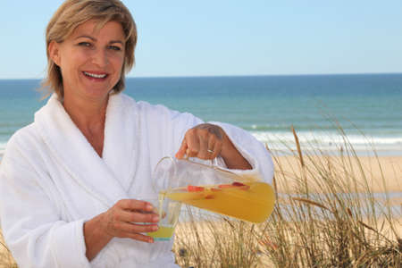 50 55: Woman pouring herself a glass of orange juice at the beach