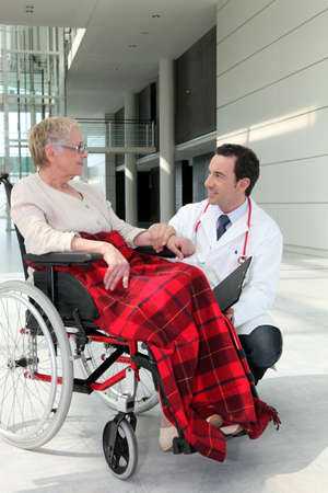 Doctor talking to an elderly woman in a wheelchair photo