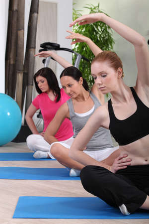 collectives: female threesome doing exercise indoors