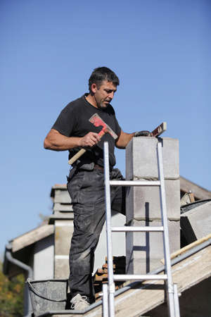 45 50 years: Tradesman building a chimney stack
