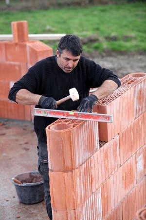 man erecting a brick wall Stock Photo - 12006046