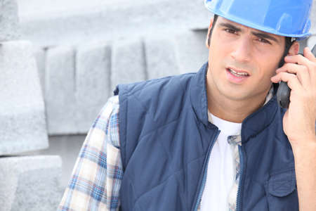 walkie: Construction worker on a call next to a pile of curbing Stock Photo