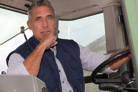 50 years old man: a farmer in a tractor cabin is driving