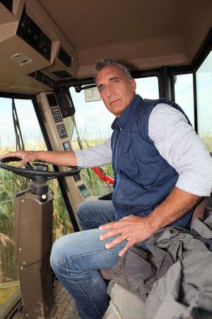 combine harvester: Farmer sentado en la cabina de una cosechadora Foto de archivo