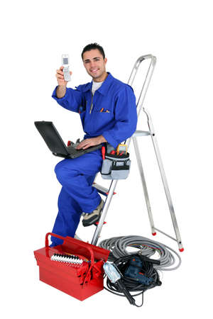 Technician with laptop and cellphone leaning on a ladder photo