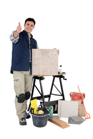 Approving tradesman posing with his tools and building materials Stock Photo - 12005437