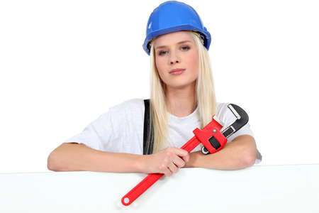 Female worker with a wrench and board left blank for your image photo