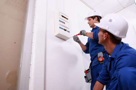 12006193: Tradesmen installing a distribution board Stock Photo