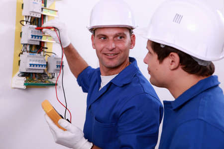 fuse box: Electrical safety inspectors verifying central fuse box Stock Photo