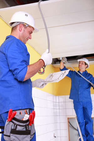 cabling: Electricians installing electrical cabling Stock Photo