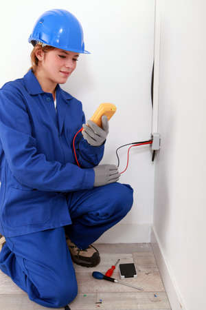 voltmeter: Female electrician using a voltmeter
