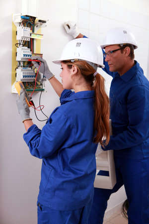 a young female electrician using an ammeter for checking an electricity meter and an older man watching her photo
