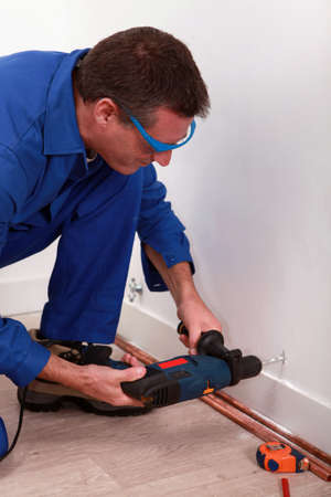 skirting: craftsman making a hole with a power drill Stock Photo