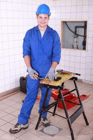 koperen leiding: Jonge arbeider meten koperen buis