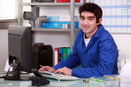 Plumber typing at a computer photo