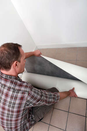 Crouching man unrolling flooring photo